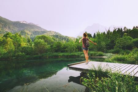 De jonge vrouw staat op een houten brug met opgeheven armen omhoog op de aardachtergrond. Reizen, vrijheid, lifestyle concept. Slovenië, Europa.