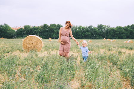 Beautiful pregnant woman and her cute toddler son having fun on wheat field with haystacks at summer day on nature, outdoors. Young mother waiting of a second baby. Pregnancy and family image. Mom and child 스톡 콘텐츠