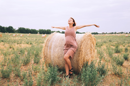 Beautiful pregnant woman in dress on nature raised arms on background of wheat field with haystacks at summer day.