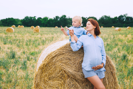 Beautiful pregnant woman and her cute toddler son having fun on wheat field with haystacks at summer day on nature, outdoors.