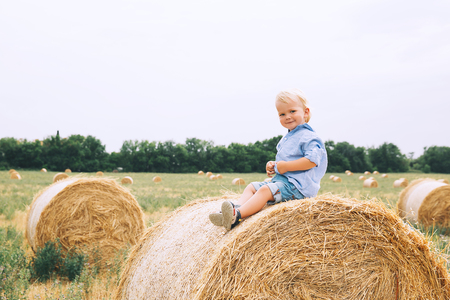 Cute toddler boy sitting on haystacks at wheat field. Happy child at summer day on nature, outdoors. Family, childhood background.