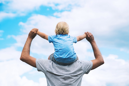 Father carrying his son on his back with raised arms up against the sky. Man and child boy. Family background. Dad and his kid having fun at summer day on nature. Back view, outdoors.