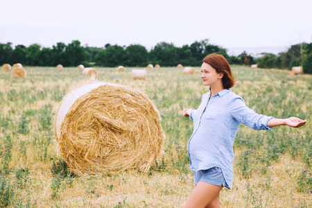 Beautiful pregnant woman in nature, outdoors. Woman with raised arms on background of wheat field with haystacks at summer day. Photo of pregnancy, maternity, expectation. Mother waiting of a baby