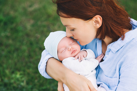 Loving mother with her newborn baby on her arms. Beautiful mom with a cute sleeping new born child on nature outdoors. Babys first week of life. Happy maternity and harmonious family. Stock Photo