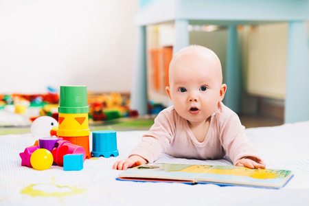 Adorable 6 months old baby looking and reading a book. Baby playing with colorful toys at home. Happy child playing and discovery. Early development, learning and education of kid Stock Photo