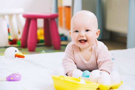 Baby playing with colorful toys at home. Happy 6 months old baby child playing and discovery. Early development, learning and education of kid