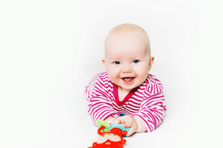 Smiling cutest baby playing with colorful toys on a white background. Happy 6 months old baby child playing and discovery. Early development, learning and education of kid