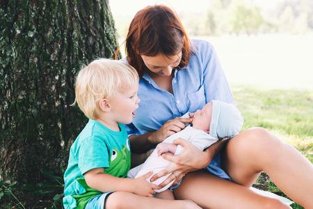 Mère avec petite fille et fils aîné sur la marche en plein air. Femme tenant un bébé nouveau-né avec un enfant plus âgé sur la nature dans le parc. Vie d'harmonie familiale. Soin et allaitement bébé. Banque d'images