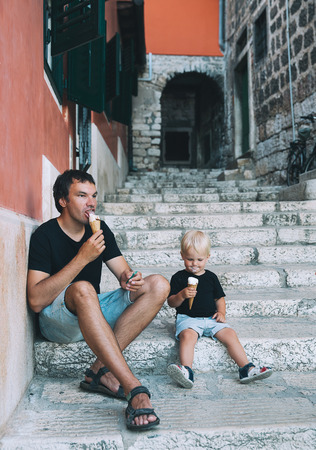 Father and son eating together ice cream outdoor. Man and kid boy with gelato at old street of Italy. Loving family and summer vacation. Stock Photo