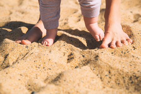 Parent and child walking barefoot. Mother and cute little baby feet on summer beach sand. Family on the beach of Tenerife island, Spain.
