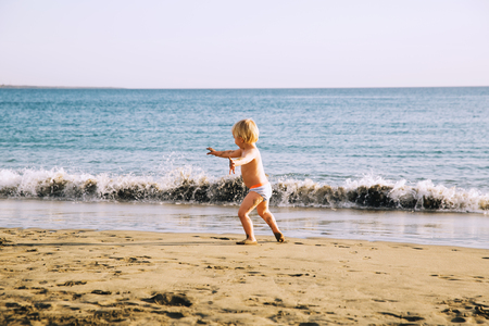 Happy child have fun in the sea beach. Kid play at the ocean. Boy running at sea shore. Summer vacation with kid. Water fun. Family holiday on Tenerife, Spain.