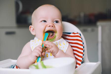 Alimentación. Bebé sonriente desordenado comiendo con una cuchara en la silla alta. Primer alimento sólido del bebé. Madre alimentando al niño pequeño con una cuchara de puré. Rutina diaria. Comer con los dedos. Nutrición infantil saludable.