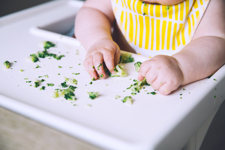 Babys first solid food. Messy smiling baby eats and tastes with fingers vegetables broccoli in high chair. Healthy child nutrition. Mother gives to try foods to feed little child 7 months old