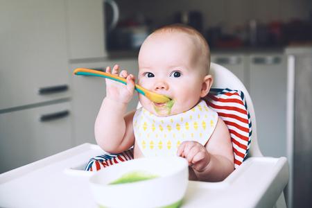 Füttern. Unordentliches lächelndes Baby, das mit einem Löffel im Hochstuhl isst. Babys erste feste Nahrung. Mutter füttert kleines Kind mit Löffel Püree. Tägliche Routine. Fingerfood. Gesunde Kinderernährung.