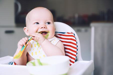Alimentation. Bébé souriant malpropre, manger avec une cuillère dans une chaise haute. Le premier aliment solide de bébé. Mère nourrissant le petit enfant avec une cuillère de purée. Routine quotidienne. Nourriture à manger avec les doigts. Alimentation saine des enfants. Banque d'images