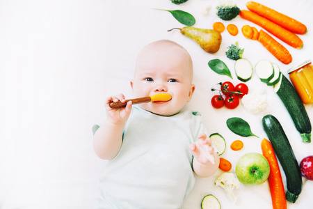 Healthy child nutrition, food background, top view. Baby 8 months old surrounded with different fresh fruits and vegetables on white background. Baby first solid feeding 스톡 콘텐츠