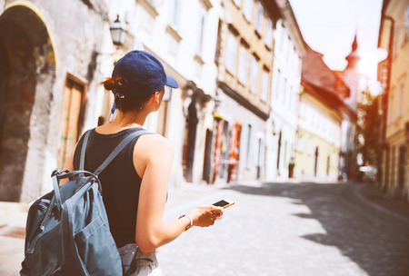 Travel Europe. Woman tourist with cup of coffee using smart phone on medieval street in Old City of Ljubljana. Girl traveler with backpack discovers Slovenia. Vacation and journey in european city.