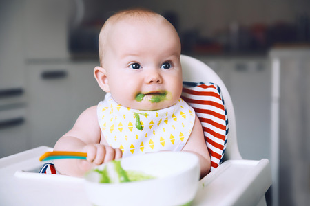 Feeding. Messy smiling baby eating with a spoon in high chair. Babys first solid food. Mother feeding little child with spoon of puree. Daily routine. Finger food. Healthy child nutrition. Banco de Imagens