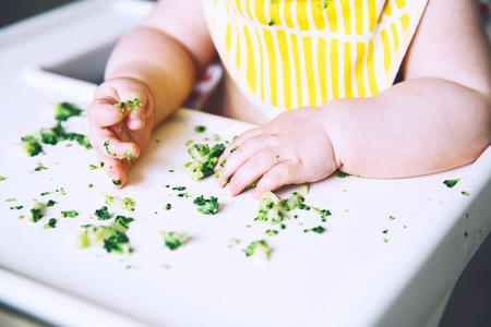 A messy smiling baby eats and tastes the broccoli with fingers on a high chair.