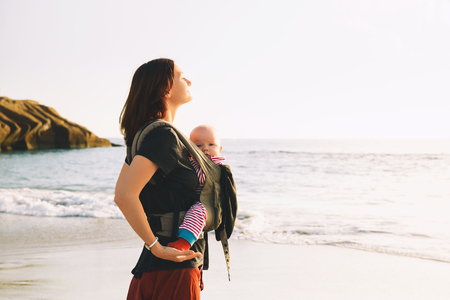 Baby and mother on sea at summer day. Happy family walking on nature outdoors. Child in a carrier backpack. Woman and her baby on coastline ocean on the island of Tenerife, Spain. Travel Europe