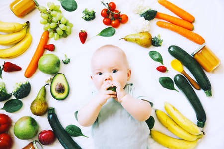 Healthy child nutrition, food background, top view. Baby 8 months old surrounded with different fresh fruits and vegetables on white background. Baby first solid feeding Stockfoto