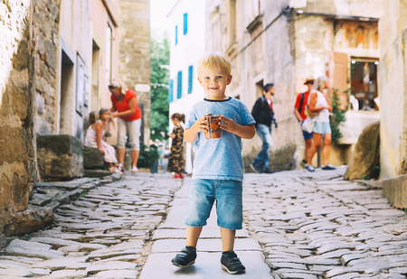 Cute kid boy with Fritule - homemade fritters with chocolate on city street of Croatia. Child eating tasty doughnuts balls - Traditional National Festive Croatian sweet pastry, cookies for tourists. Banco de Imagens