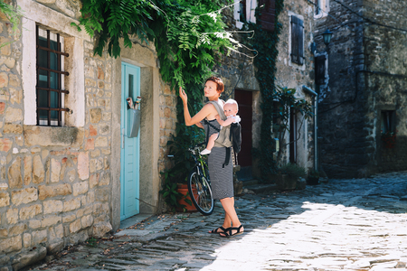 Young woman and baby in historical town of Groznjan, Croatia, Europe. Mother with cute little child on old european street. Typical medieval italian and istrian streets. Family travel Europe