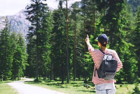 Hiker woman pointing out finger forward, back view. Outdoors on nature. Travel at Dolomites, Italy, Europe. Summer holiday in South Tyrol. Girl tourist in forest with mountains on background.