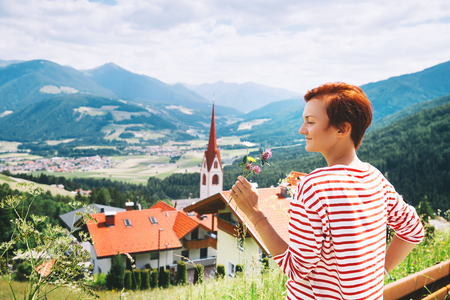 Hiker woman relaxing outdoors on nature. Travel at Dolomites, Italy, Europe. Summer holiday in South Tyrol. Girl tourist with alpines flowers with mountains and villages, church on background.