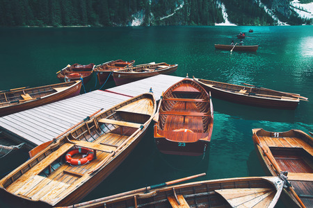 Traditional wooden rowing boats on italian alpine Braies Lake at summer. Lago Di Braies is largest natural lake in Dolomites, South Tyrol, Italy, Europe. Stock Photo - 105330291