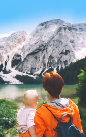 Family of tourists on walks on Braies Lake. Woman and baby girl on lake shore of Lago di Braies in Dolomites, South Tyrol, Italy, Europe. Beauty of nature image.