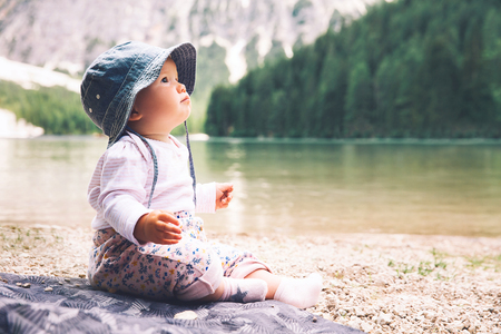Child with family on walk on Braies Lake. Cute baby girl sits on lake shore of Lago di Braies in Dolomites, South Tyrol, Italy, Europe. Beauty of nature image. Little discoverer.