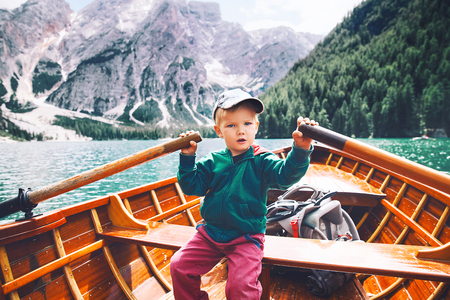 Funny child with family on walk by traditional wooden boat with oars on Braies Lake with alpine mountains on background. View on Lago di Braies in Dolomites, South Tyrol, Italy, Europe.