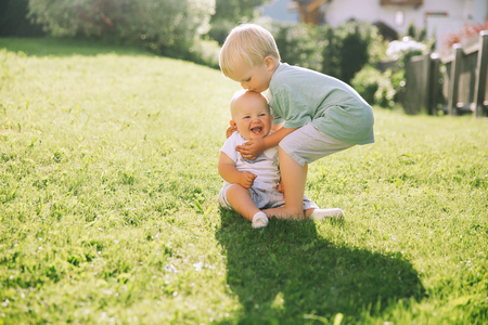 Happy children play on nature outdoors. Brother and sister have fun together at summer outside. Adorable little baby girl and child boy sitting on green nature background. Image of childhood.