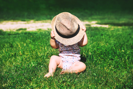 Baby in nature. Cutest little girl in green grass playing with straw hat at summertime. Image of childhood. Parents and activity with kid outdoors. Beautiful happy child sits on meadow in the park.