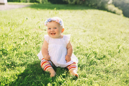 Baby at summer outside. Adorable little girl on green nature background. Image of childhood. Parents and activity with kid outdoors. Beautiful happy child have fun on grass of meadow.