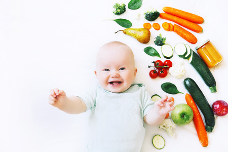 Healthy child nutrition, food background, top view. Smiling baby 8 months old surrounded with different fresh fruits and vegetables on white background. Baby first solid feeding