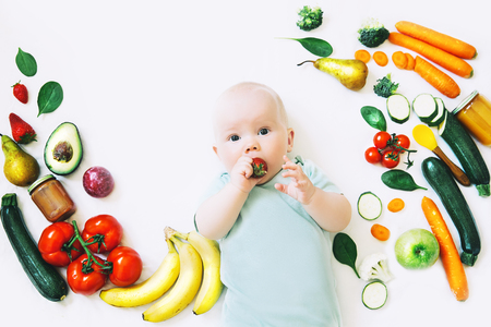 Healthy child nutrition, food background, top view. Baby 8 months old surrounded with different fresh fruits and vegetables on white background. Baby first solid feeding Imagens