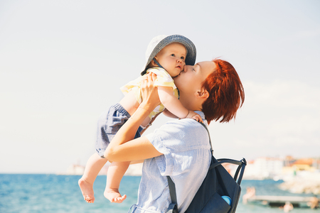 Mother with daughter having fun on coast near sea beach. Woman and baby in vacation in Piran, Slovenia, Europe. Parent and child at summer time outdoors. Happy family relaxing by the sea.