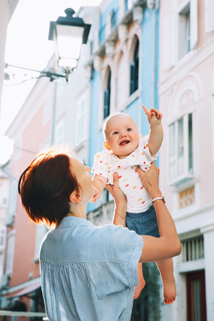 Young mother with baby on historical european streets of old town of Piran, Slovenia, Europe. Cute little child point out forward.Typical medieval italian and istrian streets. Family travel Europe. Stock Photo