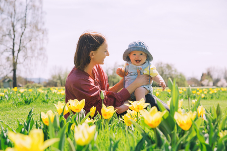 Loving mother and baby girl among yellow tulips flowers. Woman with her daughter playing outdoors in spring park. Family on nature. Image of Mothers Day, Easter. Tulip field in Arboretum, Slovenia.