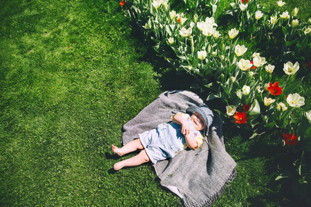 Happy smiling baby girl lying on blanket in green grass of tulips field. Child playing outdoors in spring park. Image of Mothers Day, Easter. Family on nature in Arboretum, Slovenia, Europe.