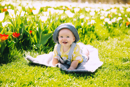 Happy smiling baby girl lying on blanket in green grass of tulips field. Child playing outdoors in spring park. Image of Mother's Day, Easter. Family on nature in Arboretum, Slovenia, Europe.