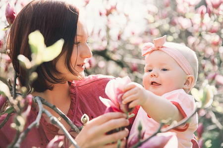 Loving mother and baby girl are smelling blooming blossom pink magnolia tree. Young beautiful mom and little daughter among garden flowers outdoors. Family on nature in Arboretum, Slovenia Stock Photo