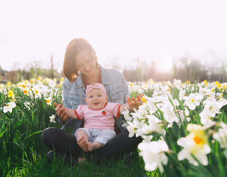 Beautiful loving mother and baby girl in daffodils flowers field at springtime. Young woman with her cute little daughter playing outdoors. Family on nature in Arboretum, Slovenia.