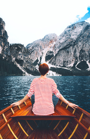 Tourist woman in traditional wooden rowing boat on italian alpine Braies Lake. Girl enjoying stunning view of Lago di Braies in Dolomites, South Tyrol, Italy, Europe. Beauty of nature background. Stock Photo