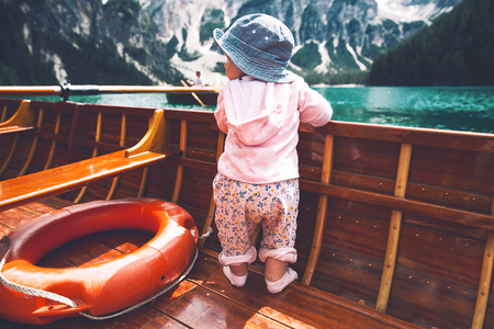 Little baby child with family on walk by traditional wooden boat with oars on Braies Lake with alpine mountains on background. View on Lago di Braies in Dolomites, South Tyrol, Italy, Europe. Stock Photo