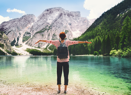 Woman with raised arms up looking at Braies Lake with mountains on background. Girl enjoying stunning view of Lago di Braies in Dolomites, South Tyrol, Italy, Europe. Beauty of nature image. Stock Photo