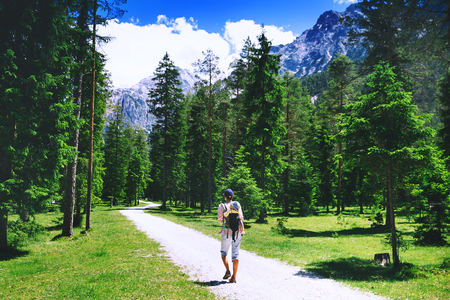 Family on trekking day in the mountains. Mother and child on nature. Tourists travel at Dolomites, Italy, Europe. Summer holiday in South Tyrol. Woman hiking with baby in carrier backpack Stock Photo