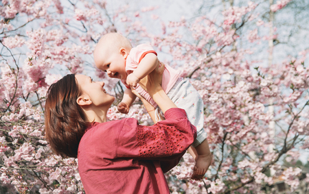 Loving mother and baby girl on background blooming pink flowers of apple tree at springtime. Beautiful woman with daughter among garden flowers outdoors. Family on nature in Arboretum, Slovenia